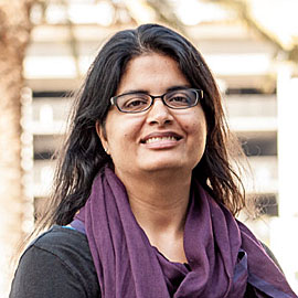 Image of Fatima Currimbhoy, a light brown-skinned female with long black hair and glasses, smiling at the camera.